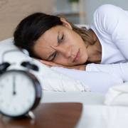 Unhappy restless woman wearing pajama suffering from insomnia, alarm clock on bedside table, sleepless tired girl with open eyes lying in bed, lack of sleep, early morning awakening concept søvn                       (Foto: Shutterstock)